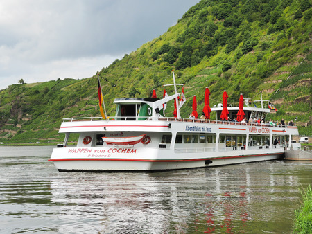 BEILSTEIN, GERMANY - AUGUST 14, 2014: excursion boat near Beilstein village, Moselle river region. Village is in Cochem-Zell district in Rhineland-Palatinate, Germany, it was was settled about AD 800.