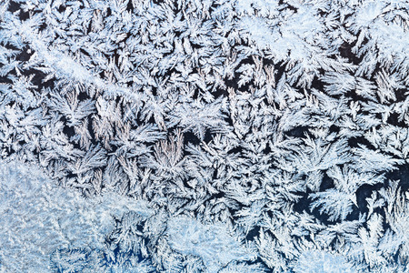 winter background - snowflakes and frost on frozen window