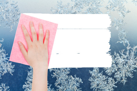 weather concept - hand deletes winter snowflake on window by pink rag from image and white empty copy space are appearing