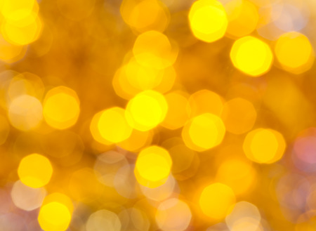 abstract blurred background - yellow shimmering Christmas lights bokeh of electric garlands on Xmas tree