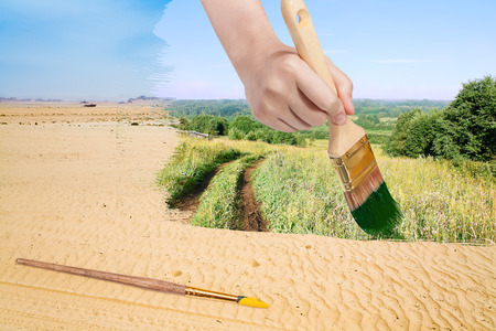 nature concept - seasons and weather changing: hand with paintbrush paints green countryside in sand desert