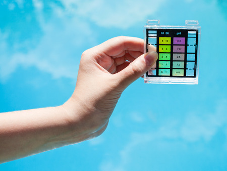 Photo pour check water pollution in blue outdoor pool by chemical tester - image libre de droit