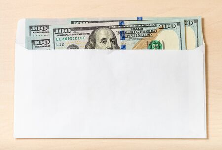 several united states one hundred-dollar bills in open mail envelope on wooden table