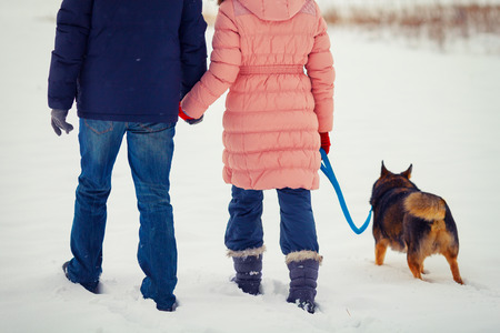 Young happy couple with dog walking in the snowy field back to camera