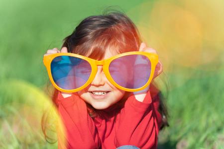 Photo pour Happy smiling little girl wearing big sunglasses in the field - image libre de droit
