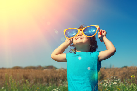 Photo pour Little girl with big sunglasses enjoys sun - image libre de droit