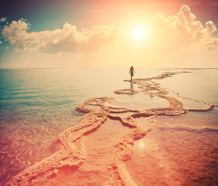Photo pour Silhouette of young woman walking on Dead Sea - image libre de droit
