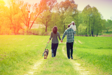 Photo pour Happy family with dog walking on the rural dirt road. Little girl sitting on dad's shoulder - image libre de droit