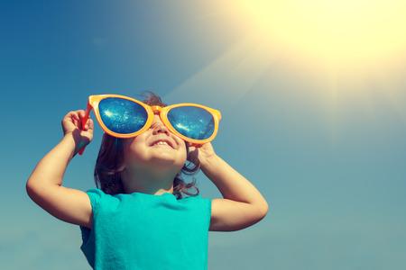 Foto de Happy little girl with big sunglasses looking at the sun - Imagen libre de derechos