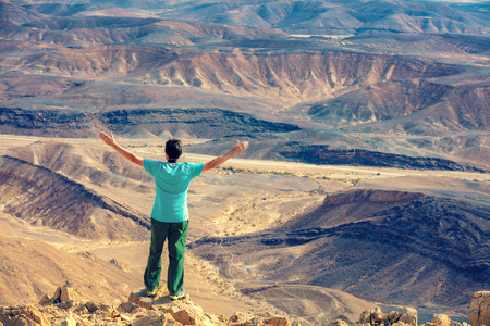 Photo for A man with hands in the air standing on the cliff in the desert - Royalty Free Image