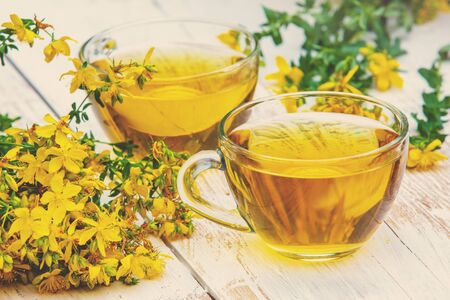 Photo pour Two cups of Hypericum herbal (Tutsan) tea on wooden grunge table - image libre de droit