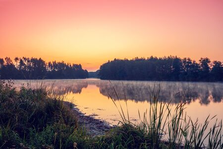 Photo pour Magical dawn over the lake with a beautiful reflection on the water. Serene lake in the early morning. Nature landscape - image libre de droit