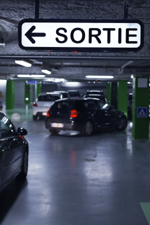 Underground parking with cars and exit sign