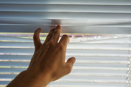 Photo pour Human hand opens the white blinds. A man looks at the street through the blinds - image libre de droit