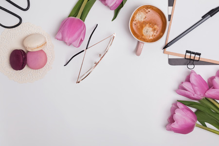 Photo pour Beautiful pink tulips, cup of coffee and macarons on the white table - image libre de droit