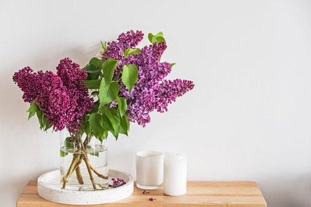 Photo pour Bouquet of beautiful lilac flowers standing in a glass vase on the small wooden stand - image libre de droit