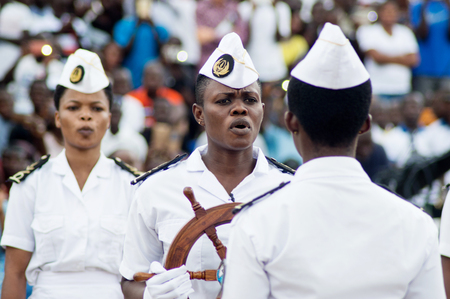 Abidjan, Ivory Coast - August 3, 2017: shoulder pad ceremony to students leaving the Maritime Academy. group of marine women dressed in white receiving a ship's steering wheel as a symbol
