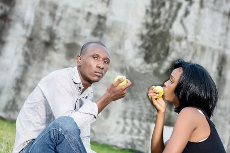 Photo pour happy young couple at the park sitting entwined and sharing a green apple - image libre de droit