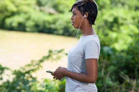 Foto de Young sporty woman listens music on mobile phone after workout at park - Imagen libre de derechos