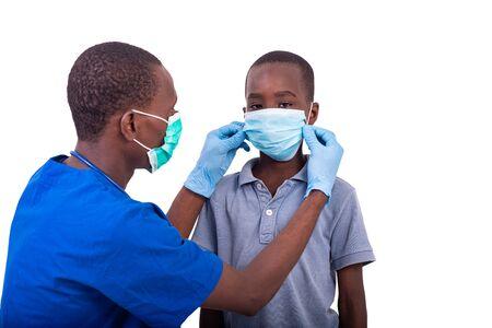 Foto de young male doctor in protective suit, wearing medical mask on child's face. - Imagen libre de derechos