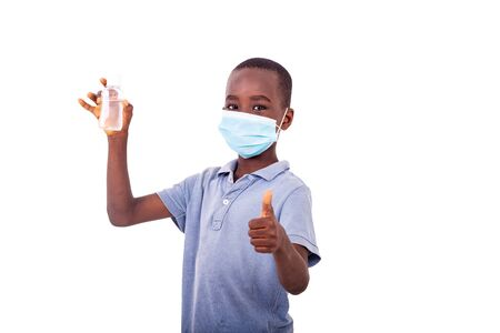 Photo pour a little boy with a medical mask holding an antibacterial gel while showing his thumb. - image libre de droit