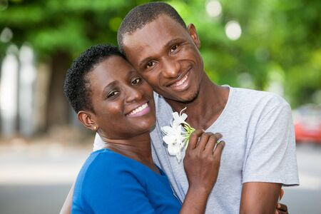 Foto per young couple standing with flower in hand embraced look at camera laughing. - Immagine Royalty Free