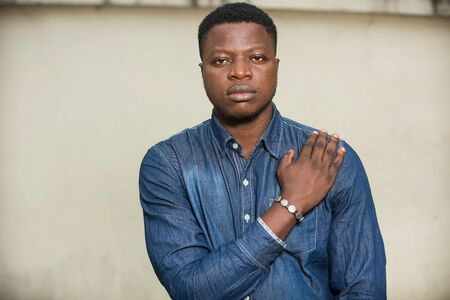 Photo pour young african man standing in jeans shirt looking at the camera. - image libre de droit