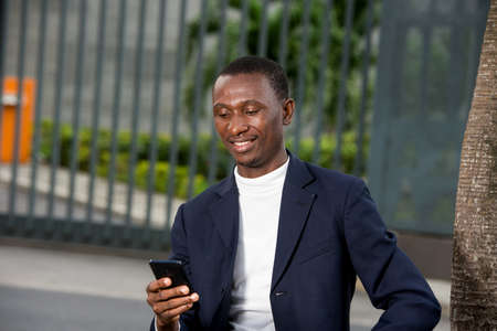 Photo pour young african man sitting in a suit looking at mobile phone while smiling. - image libre de droit