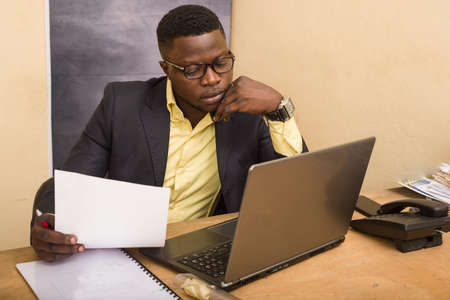 Photo pour young man in glasses sitting at desk looking at laptop with paper in hand. - image libre de droit