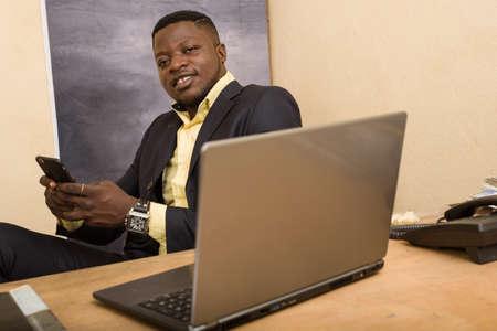 Photo pour young businessman sitting at desk with mobile phone smiling. - image libre de droit