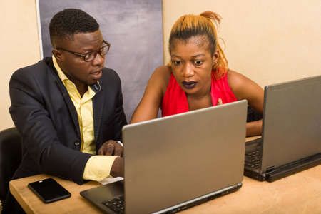 Photo pour Teamwork: Businessman and businesswoman working as a team in office, they discuss and work on laptop. - image libre de droit