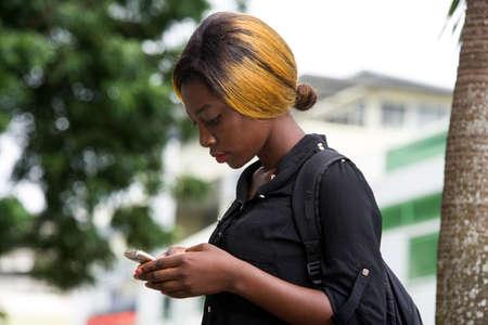 Photo pour Female student checking messages on mobile phone outside college buildings - image libre de droit