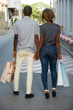 Photo pour Portrait of a happy couple with shopping bags walking together in city. - image libre de droit