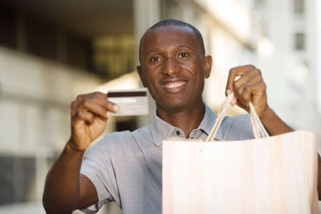 Photo pour smiling man showing and holding shopping bags with credit card outdoors - image libre de droit