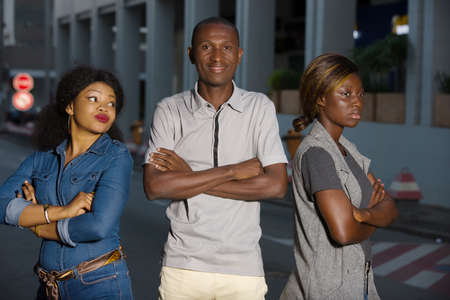 Photo pour two jealous women are fighting a man. Divorce of a couple outdoors in the city man standing between two angry girlfriends is watching the camera - image libre de droit