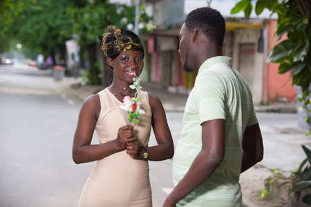 Photo pour romantic offer to get married. A man makes a surprise to his girlfriend in the city. Valentine's day proposal concept. Young man giving a flower for girlfriend on Valentine's Day. - image libre de droit