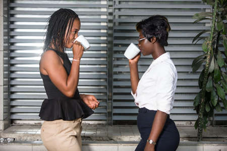 Photo pour two businesswomen drinking coffee outdoors. Work Balance Concept - image libre de droit