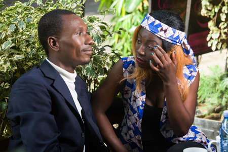 Photo pour young african couple sitting in a park looking at each other smiling. - image libre de droit