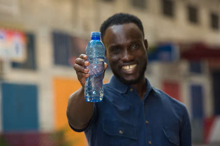 Photo pour young man standing outdoors presenting a bottle of water while smiling. - image libre de droit