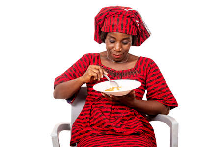 Photo pour beautiful adult woman wearing a suit of loincloth while sitting on a chair eating an African meal while being smiling - image libre de droit