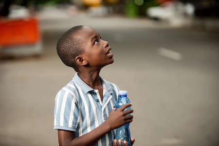 Photo pour happy little African boy standing sideways holding a plastic bottle and looking up - image libre de droit