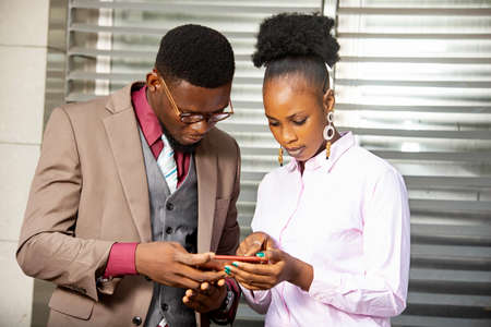 Photo pour two young business partner standing and working with a mobile phone while smiling - image libre de droit