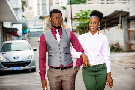 Photo pour happy young african couple walking while standing talking hand in the street outdoors while being smiling - image libre de droit