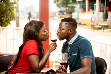 Photo pour young couple sitting outside a refreshment bar giving kiss to a glass of wine. - image libre de droit
