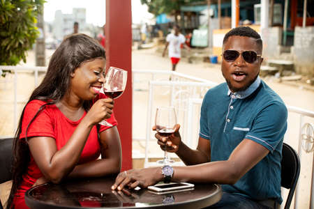 Photo pour young african couple sitting in a refreshment bar laughing holding glasses of wine. - image libre de droit