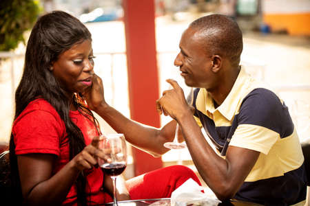 Photo pour young couple in love sitting outside a refreshment bar being cuddled with glasses of wine in hand smiling. - image libre de droit