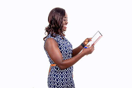 Photo pour young african woman holding a notebook while smiling; teenage student girl standing on a white background, beautiful beautiful black complexion - image libre de droit