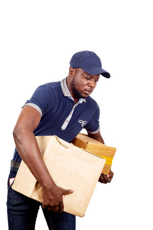 Photo pour young delivery man standing in hat on white background carrying heavy cardboard boxes. . - image libre de droit