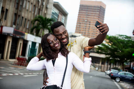 Photo pour young couple standing outdoors photographing themselves with mobile phone while smiling. - image libre de droit