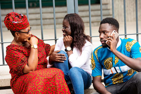 Photo pour young man in traditional clothes sitting outdoors communicating on mobile phone while his mother and sister chatting laughing. - image libre de droit